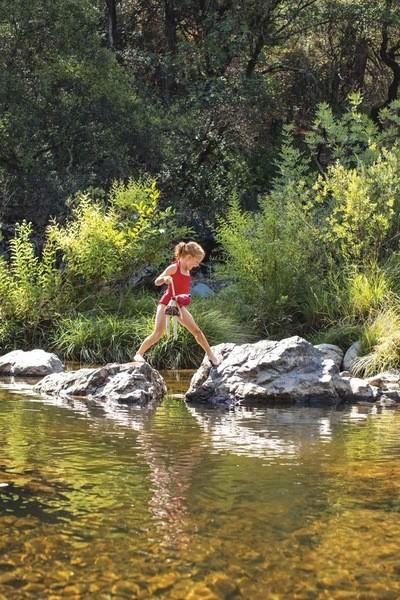 Mädchen versucht mit ihrer Puppe in der Hand, mit Hilfe von großen Steinen, einen Fluss zu überqueren