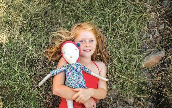 Mädchen mit Sommersprossen liegt mit ihrer Puppe im Arm auf einer Wiese und schaut nach oben