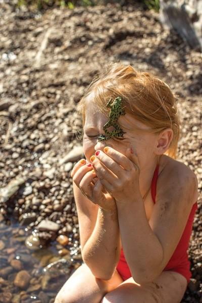 Mädchen im Badeanzug am Flussufer mit Frosch im Gesicht