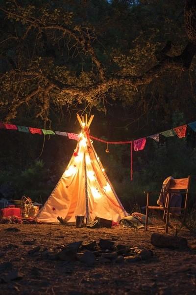 Ein hell erleuchtetes, bunt geschmücktes Zelt vor einem erloschenen Lagerfeuer