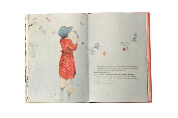 Barfüßiges Mädchen im rotgepunkteten Kleid mit Mütze, hängt die unterschiedlichsten Gegenstände an Wäscheleine