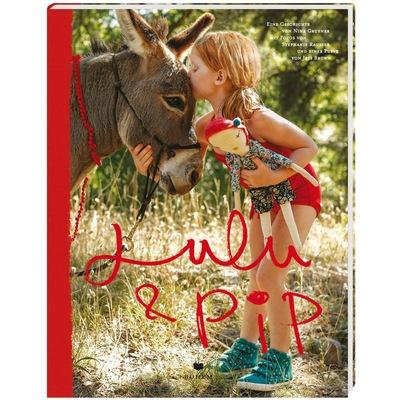 Mädchen auf der Wiese mit Puppe in der Hand küsst Esel auf die Stirn
